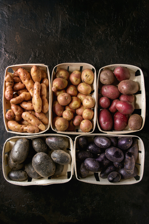 Variety of raw uncooked organic potatoes different kind and colors red, yellow, purple in market baskets over dark texture background. Top view, space Banco de Imagens - 94902910