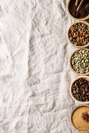 Variety of grounded, instant coffee, different coffee beans, brown sugar, spices in wooden bowls in row over white linen textil as background. Top view, space