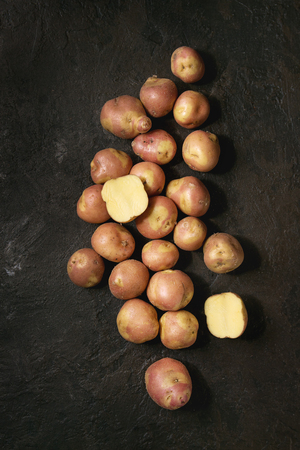 Raw uncooked organic potatoes named miss blush, whole and slice over dark texture background. Top view, copy space Banco de Imagens