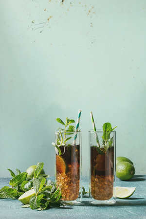 Two Glasses of classic Cuba libre cocktail with lime, mint, crushed ice and cola, ingredients above, cocktail tubes over turquoise green pin-up style background. Sunlight, space. Toned image