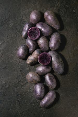 プルネルと名付けられた生の紫色の調理されていない有機ジャガイモは、全体と暗いテクスチャの背景の上にスライス。トップビュー、コピースペ