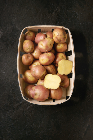 Raw uncooked organic potatoes named miss blush, whole and slice, in market baskets over dark texture background. Top view, copy space Banco de Imagens