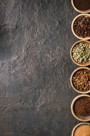 Variety of grounded, instant coffee, different coffee beans, brown sugar in wooden bowls in row over dark texture background. Top view, space