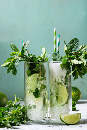 Two glasses of classic and coconut milk mojito cocktail with fresh mint, limes, crushed ice, retro cocktail tubes with ingredients above. Pin up style, sunlight, green background.