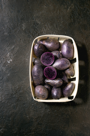 Raw purple uncooked organic potatoes named prunelle, whole and slice, in market baskets over dark texture background. Top view, copy space Banco de Imagens