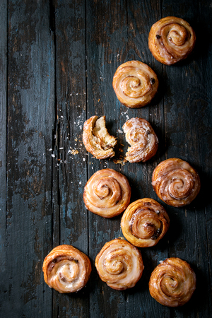 Homemade glazed puff pastry cinnamon rolls with custard and raisins over old dark blue wooden background. Top view, space. Rustic style