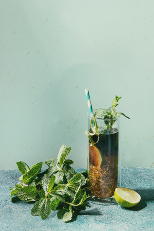 Glass of classic Cuba libre cocktail with lime, mint, crushed ice and cola, served with ingredients above, cocktail tubes over turquoise green pin-up style background. Sunlight, space. Toned image