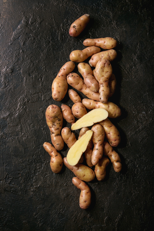 Raw uncooked organic potatoes named bayard, whole and slice over dark texture background. Top view, copy space Imagens