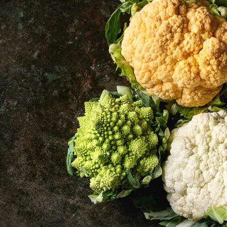 Variety of fresh raw organic colorful cauliflower and cabbage romanesco over dark texture background. Top view with space. Healthy eating concept. Square image