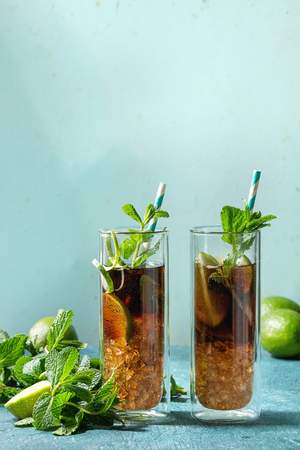 Two Glasses of classic Cuba libre cocktail with lime, mint, crushed ice and cola, served with ingredients above and retro cocktail tubes over turquoise green pin-up style background. Sunlight, space