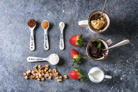 Chocolate and vanilla caramel mug cakes from microwave with fresh strawberries and ingredients in spoons above over blue texture background. Top view, space. Food knolling