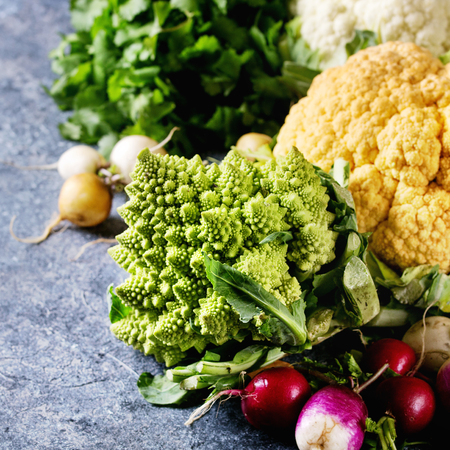 Variety of fresh raw organic colorful cauliflower, cabbage romanesco and radish with bundle of coriander over dark texture background. Close up with space. Healthy eating concept. Square image Imagens