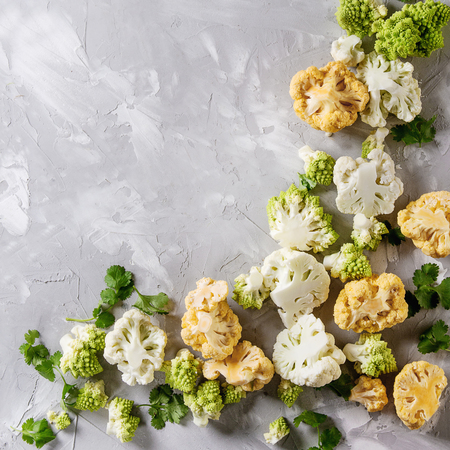 Variety of fresh raw organic colorful cauliflower, cabbage romanesco and coriander leaves over gray texture surface. Food frame background. Top view with space. Healthy eating concept. Square image