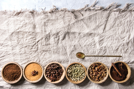 Variety of grounded, instant coffee, different coffee beans, brown sugar, spices, spoon in wooden bowls in row over white linen textil as background. Top view, space Reklamní fotografie