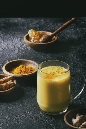 Cup of ayurvedic drink golden milk turmeric latte with curcuma powder and ingredients above over black texture background. Toned image