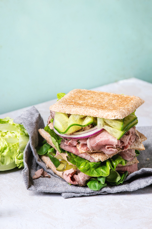 Beef and vegetables sandwiches with sliced meat, cucumber, green salad, rye whole grain bread in stack on textil napkin over grey green pin-up style background. Ingredients above
