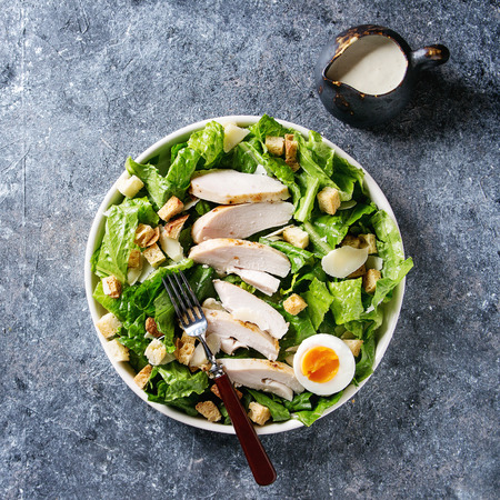 Classic Caesar salad with grilled chicken breast and half of egg in white ceramic plate. Served with croutons and dressing over dark gray texture background. Top view, space. Square image Stock Photo