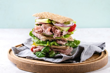 Beef and vegetables sandwiches with sliced meat, cucumber, green salad, rye whole grain bread in stack on wooden tray with textil napkin over grey green pin-up style background. Stock Photo