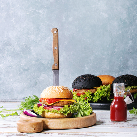 Set of homemade burgers in black and white buns with avocado, tomato sauce, lettuce, arugula, cheese, onion on wood serving board over white wooden plank table. Rustic style. Square image