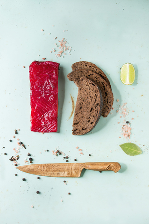 Piece of beetroot marinated salted salmon with sliced rye bread, pink salt, pepper, lime and wooden knife over light green pin-up style background. Top view, space. Food knolling