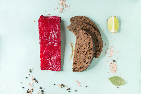 Piece of beetroot marinated salted salmon with sliced rye bread, pink salt, pepper and lime over light green pin-up style background. Top view, space. Food knolling