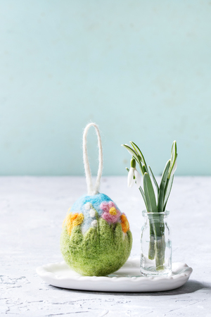 Craft felting Easter egg with blooming flower and green grass decor standing with spring snowdrops bouquet in glass bottle on grey table. Easter decoration and gifts. Copy space Stock Photo