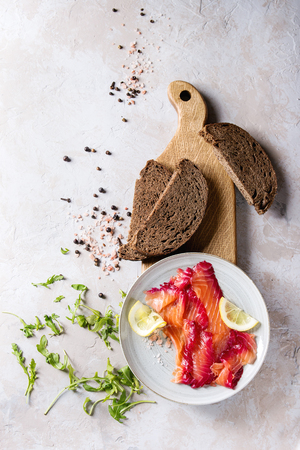 Sliced beetroot marinated salmon for sandwiches with sliced rye bread, pink salt, pepper, greens and lemon served on wooden cutting board over grey texture background. Top view, space
