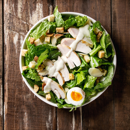 Classic Caesar salad with grilled chicken breast and half of egg in white ceramic plate. Served with croutons and dressing over old wooden background. Top view, space. Square image Stock Photo