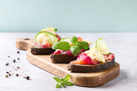 Sliced beetroot marinated salmon sandwiches with rye bread, cucumber, basil and lemon served on wooden cutting board over grey blue texture background. Close, up, space Stock Photo