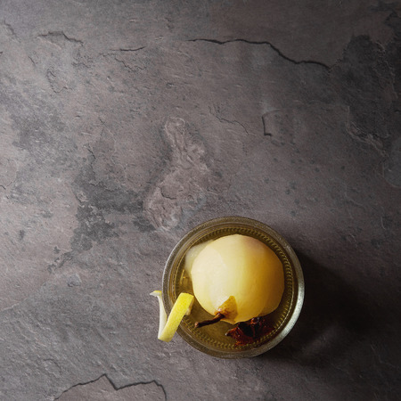 Traditional dessert poached pear in white wine served in glass bowl with syrup and lemon zest over gray texture table. Top view with space. Square image