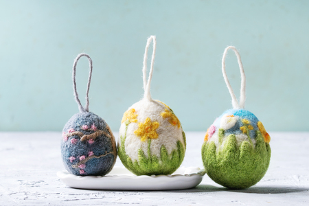 Set of craft felting Easter eggs with blooming flower sakura and green grass decor standing on grey table. Easter decoration and gifts. Copy space Archivio Fotografico