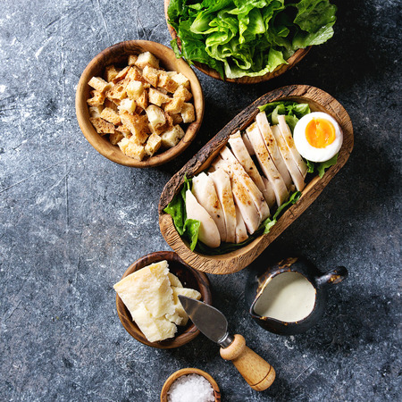 Bowls of ingredients for cooking classic Caesar salad. Sliced chicken breast, green roman salad, parmesan cheese, egg, croutons, salt, jug of sauce over grey background. Top view, space. Square image Imagens