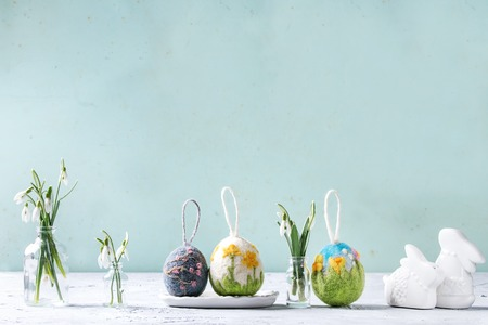 Set of craft felting Easter eggs with blooming flower sakura and green grass decor standing with spring snowdrops bouquet in glass bottle on grey table. Easter decoration and gifts. Copy space