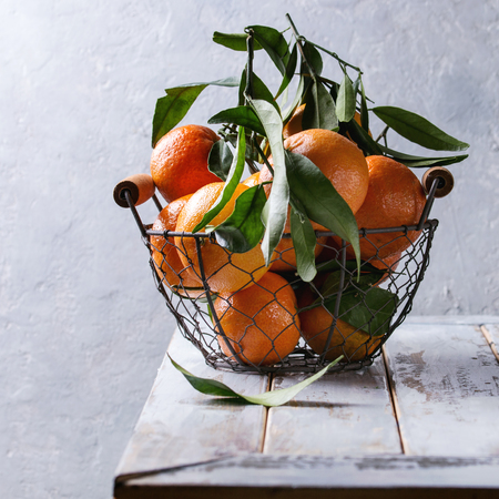Ripe organic clementines or tangerines with leaves in basket standing on white wooden plank table with gray wall as background. Rustic style. Healthy eating. Square image