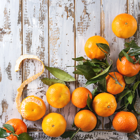 Ripe organic clementines or tangerines with leaves over white wooden plank table as background. Top view, space. Healthy eating. Square image