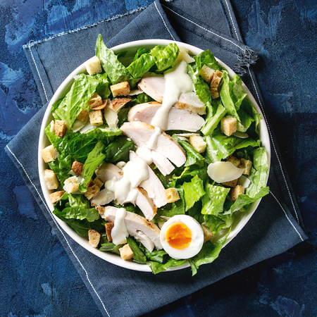 Classic Caesar salad with grilled chicken breast and half of egg in white ceramic plate. Served with croutons and dressing on cloth napkin over dark blue texture background. Top view, space. Square image Stock Photo