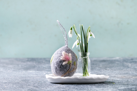 Craft felting Easter egg with blooming magnolia tree flower over grey decor standing with spring snowdrops bouquet in glass bottle on grey table. Easter decoration and gifts. Copy space