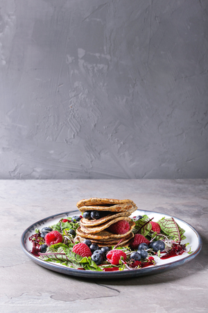 Vegan chickpea pancakes served in plate with green salad young beetroot leaves, sprouts, berries, berry sauce over grey kitchen table. Copy space. Healthy eating Archivio Fotografico - 96377201