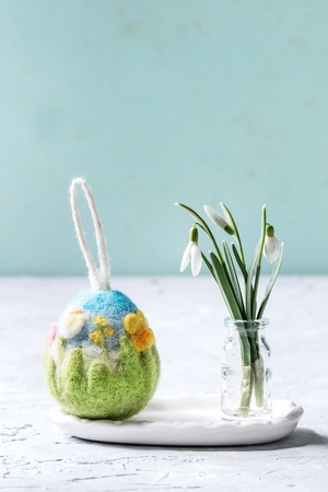 Craft felting Easter egg with blooming flower and green grass decor standing with spring snowdrops bouquet in glass bottle on grey table. Easter decoration and gifts. Copy space Zdjęcie Seryjne