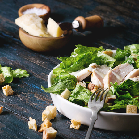 Classic Caesar salad with grilled chicken breast and half of egg in white ceramic plate. Served with fork and ingredients above over old dark blue wooden background. Rustic style. Square image