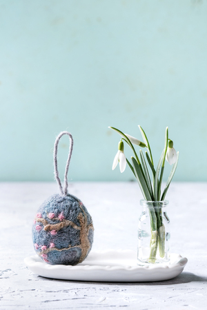 Craft felting Easter egg with blooming sakura tree over grey decor standing with spring snowdrops bouquet in glass bottle on grey table. Easter decoration and gifts. Copy space Stock Photo