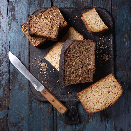 Variety loaves of sliced homemade rye bread whole grain and seeds with knife on black cutting board over old dark wooden background. Top view, space. Healthy eating. Square image