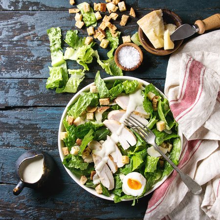 Classic Caesar salad with grilled chicken breast and half of egg in white ceramic plate. Served on towel with ingredients above over old dark blue wooden background. Top view, space. Square image