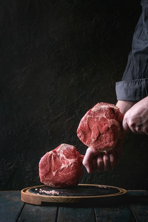 Man's hands holding raw uncooked black angus beef tomahawk steaks on bones with salt and pepper on round wooden slate cutting board over dark wooden plank table. Rustic style Archivio Fotografico - 96693028