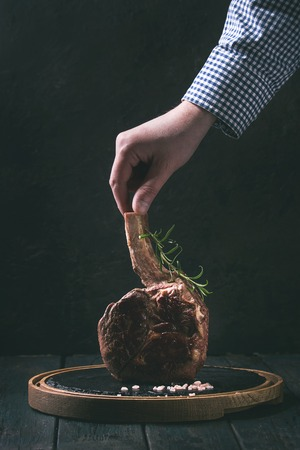 Man's hand holding grilled black angus beef tomahawk steak on bone served with salt, pepper and rosemary on round slate cutting board over dark wooden plank kitchen table. Copy space. Toned image Stock Photo