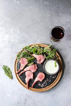 グリーンサラダの若いビートルートの葉、赤ワインのグラス、灰色のテクスチャーの背景に丸い木製スレートボードにピンクの塩を添えたヨーグル