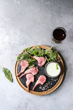Grilled sliced rack of lamb with yogurt mint sauce served with green salad young beetroot leaves, glass of red wine, pink salt on round wooden slate board over grey texture background. Top view, space