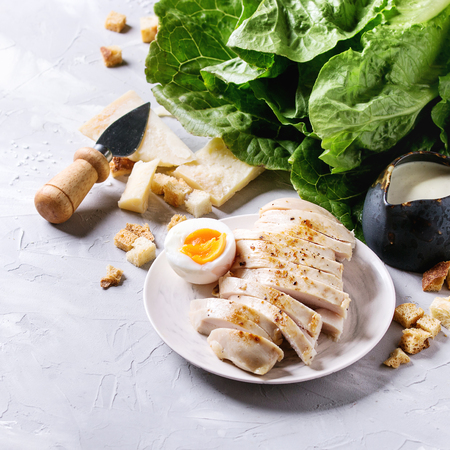 Ingredients for cooking classic Caesar salad. Sliced baked chicken breast, green roman salad, parmesan cheese, boiled egg, croutons, salt, jug of sauce over gray texture background. Square image