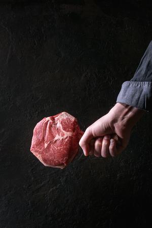Man's hands holding raw uncooked black angus beef tomahawk steak on bone over dark background. Rustic style Archivio Fotografico - 96693960