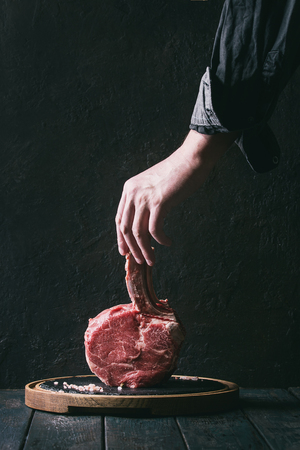 Man's hands holding raw uncooked black angus beef tomahawk steak on bone with salt and pepper on round wooden slate cutting board over dark wooden plank table. Rustic style. Toned image Archivio Fotografico - 96693980